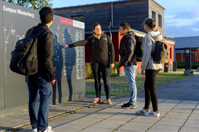 Eine Person zeigt anderen Personen den Übersichtsplan am Campus