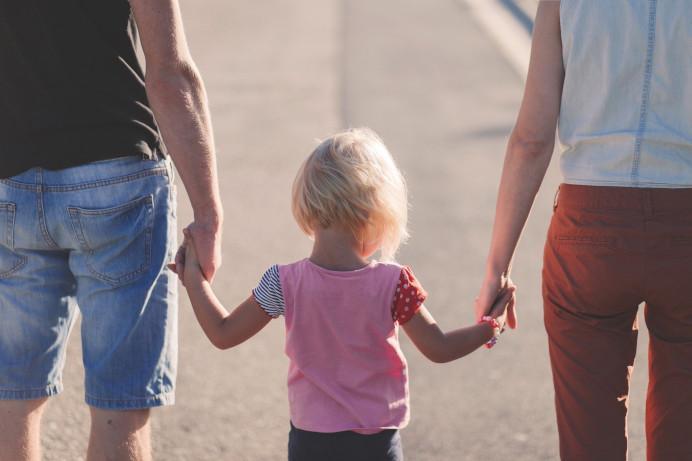 Zwei erwachsene halten ein Kind in der Mitte die Hände